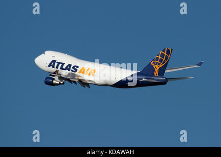 Atlas Air Boeing 747-400F cargo jet plane in flight against a blue sky. Air freight transport and supply chain management. - Stock Photo