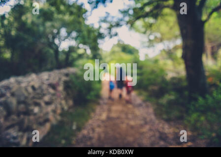 Family hiking on country road with rock fence and woods. Mother and daughters are trekking through rough terrain - Stock Photo