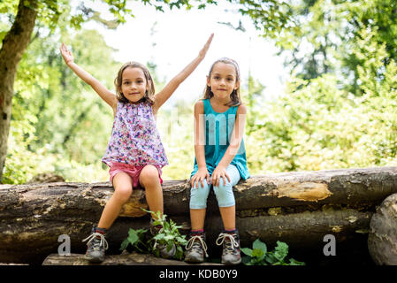 Children - twin girls are hiking in the mountains. Active family, parents and children mountaineering in the nature. - Stock Photo