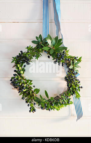 Christmas green wreath of evergreen and berries on wooden background. Hanging from a blue and white striped ribbon - Stock Photo