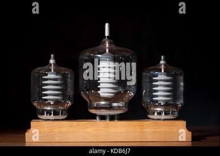 Three old vacuum transmitting tubes in front of a black background - Stock Photo