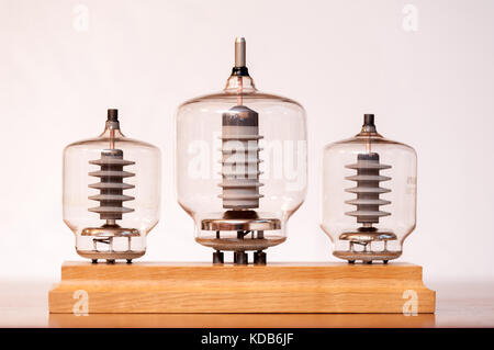 Three old vacuum transmitting tubes in front of a white background - Stock Photo