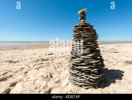 Tower made of flat stones on a sandy beach on a sunny day - Stock Photo