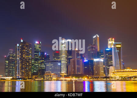 View of Singapore Downtown Core reflected in a river - Stock Photo