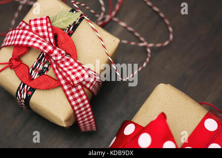 Christmas gifts, retro decoration, stars and red checkered ribbon, wrapped in craft paper - Stock Photo