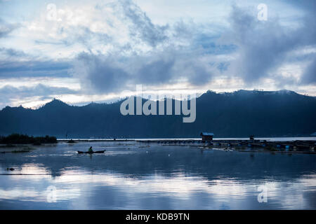 A fisherman in his boat at the Lake Buyan, Bali, Indonesia. - Stock Photo