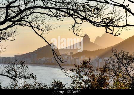 Copacabana beach in Rio de Janeiro during sunset between the vegetation on the hill - Stock Photo