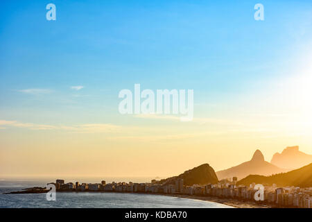 Copacabana beach in Rio de Janeiro during sunset with its buildings and the mountains in the background - Stock Photo