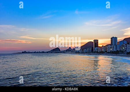 Leme and Copacabana beaches in Rio de Janeiro during sunset with its buildings, and the mountains in the background - Stock Photo