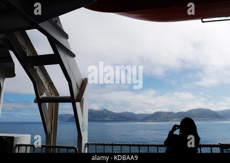 Passengers aboard Interislander Ferry crossing Cook Strait taking photo of  Sinclair Head, South of Wellington in - Stock Photo