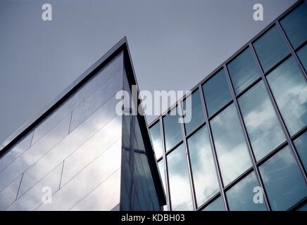 Architecture. Low angle viewpoint of glass façade  section of modern commercial building. - Stock Photo