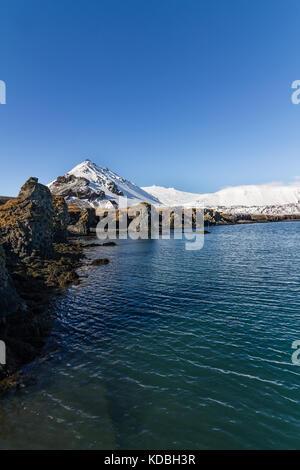 Arnarstapi harbor with Volcano glacier Snaefellsjokull in the background - Stock Photo