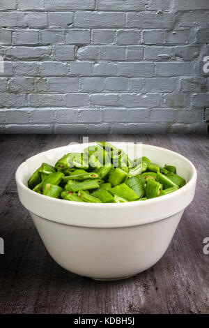 Chopped runner beans in a china bowl on a wooden table - Stock Photo