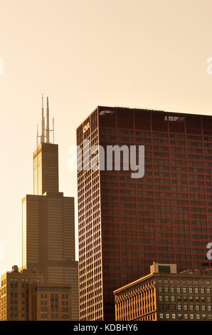 The setting sun illuminates two dominating buildings in a portion of the Chicago skyline, including, at left the - Stock Photo