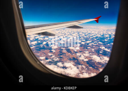 Looking through window aircraft during flight, cloudy sky - Stock Photo