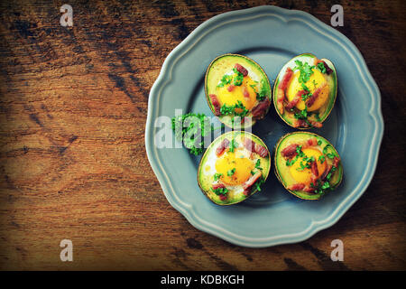 Avocado Egg Boats with bacon on dark wooden background. Top view - Stock Photo