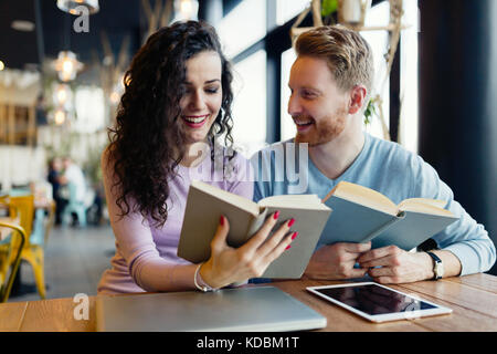 Young students spending time in coffee shop reading books - Stock Photo
