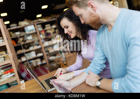 Happy couple spending time at coffee shop working on laptop - Stock Photo