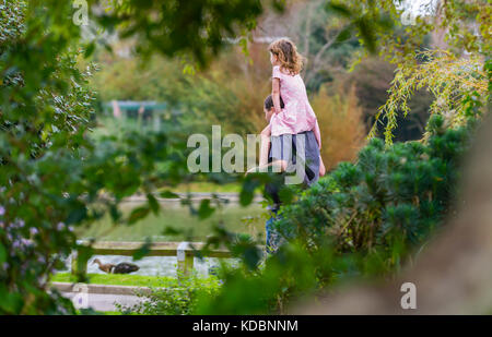 Young girl being carried on a man's shoulders, a piggy back ride, through a park in the UK. - Stock Photo
