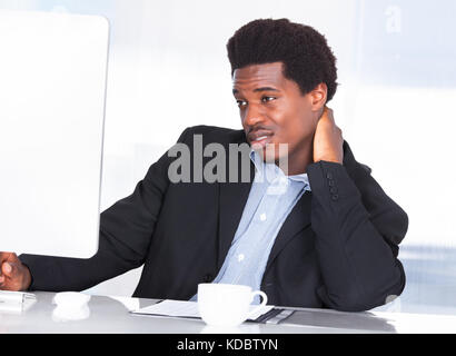 Portrait Of A Businessman Suffering From Neck Pain In Office - Stock Photo