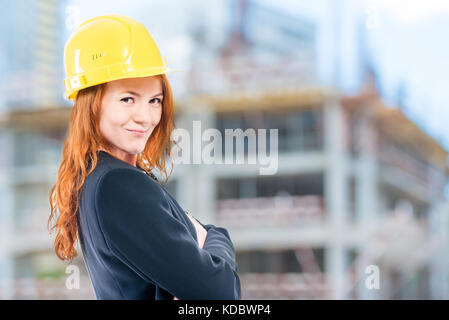 portrait of a female architect in a yellow helmet at a construction site - Stock Photo
