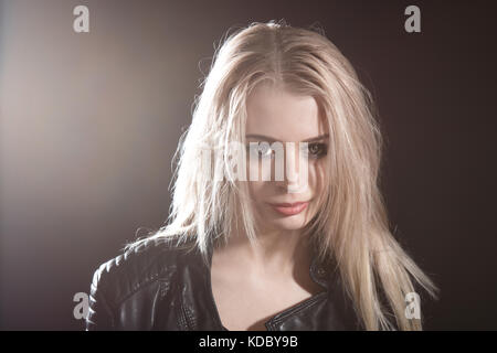 Portrait of a pretty young girl over black background - Stock Photo