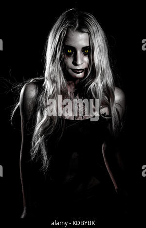 Pale bloody woman with yellow eyes over black background - Stock Photo