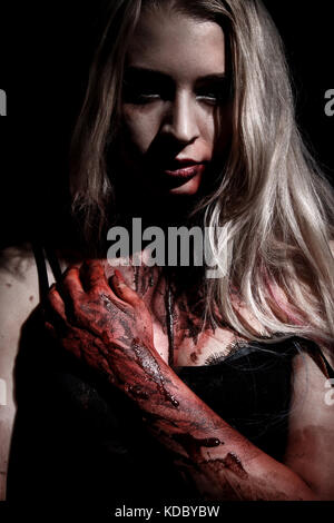 Pale bloody woman over black background - Stock Photo