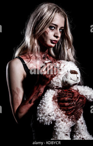 Bloody young woman holding a teddy bear over black background - Stock Photo