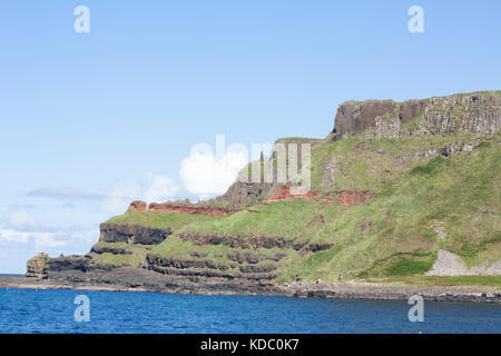 Giants Causeway Northern Ireland view with blue sky green grass on mountain with sea in view - Stock Photo