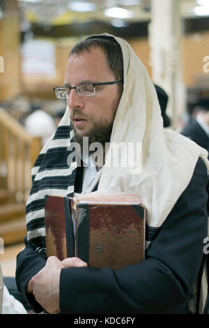 A religious Jewish man in fervent prayer at a synagogue in Brooklyn, New York - Stock Photo