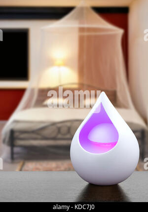 Colored air freshener in glass container in Cosi vintage bedroom with mosquito Net - Stock Photo