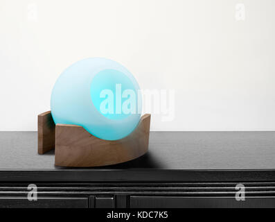 colored air freshener in glass container on black desk - Stock Photo