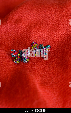 Colorful handmade earrings, butterflies, isolated on red fabric background - Stock Photo