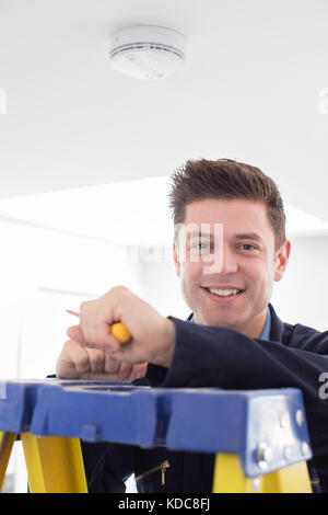 Man Installing Smoke Or Carbon Monoxide Detector - Stock Photo