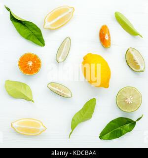 Mixed fresh citrus fruits and leaves background. Fresh lemons, lemon slice ,lime and orange on white wooden table - Stock Photo