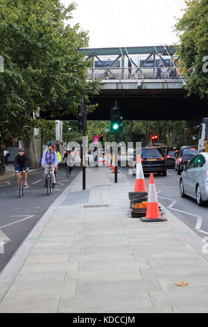 Cyclists in a segregated lane, and traffic on the Embankment in London, England, UK - Stock Photo