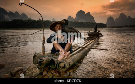 Cormorant fisherman and his birds on the Li River in Yangshuo - Stock Photo