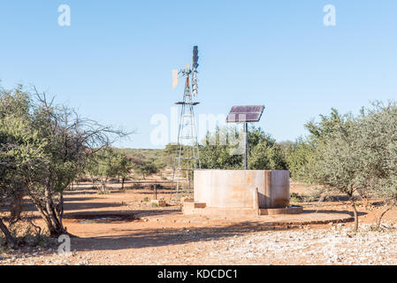 A water-pumping windmill and solar panels for a waterpump near Schmidtsfrift, a village in the Northern Cape Province - Stock Photo