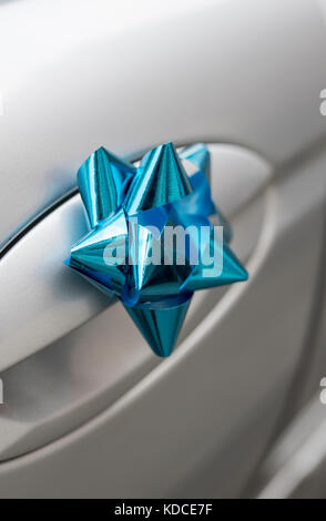 Close up of a blue wedding bow on the handle of a silver wedding car - Stock Photo