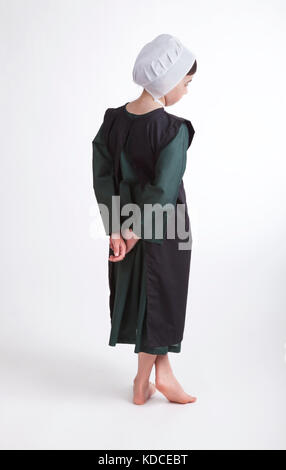 A young barefoot Amish girl in a green and black outfit isolated on a background - Stock Photo