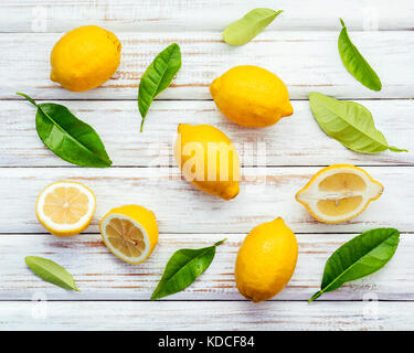 Fresh lemons and  lemons leaves on rustic wooden background. Fresh lemons and lemon slice on wooden table with flat - Stock Photo