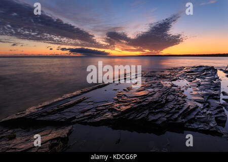 A dramatic sunrise over Lake Superior at Union Bay Campground in the Porcupine Mountain Wilderness Area - Stock Photo