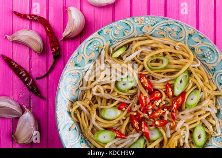 Chinese Style Wok Stir Fried Egg Noodles with Beansprouts and Red Chilli On A Pink Wooden Background - Stock Photo