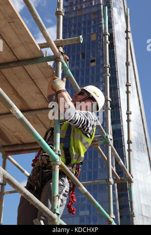 A scaffolder erects a temporary work platform on a tower block high above London. Shows The Shard in the background. - Stock Photo