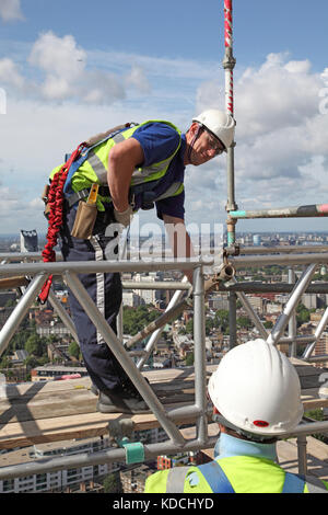 Two scaffolding erectors assemble a temporary work platform on a tower block high above London. Shows correct safety - Stock Photo