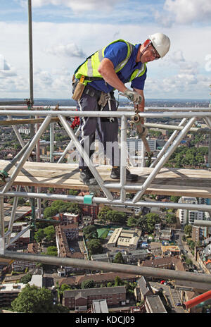A scaffolder erects a temporary work platform high above London during the refurbishment of Guys Hospital tower. - Stock Photo
