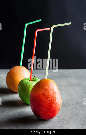 Whole Organic Ripe Fruits Tropical Mango Apple Grapefruit with Drinking Straws Fresh Natural Juices Healthy Diet - Stock Photo
