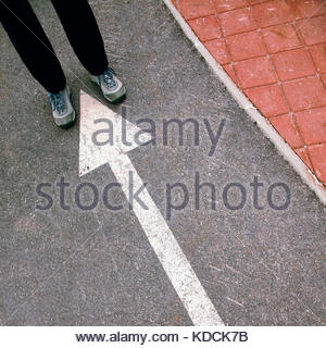Man feet on asphalt pavement arrow sign. - Stock Photo