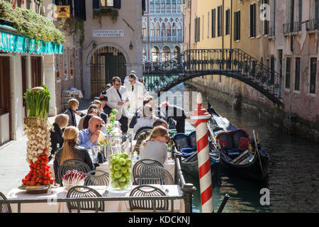 Tourists dining at the popular outdoor  Ristorante da Raffaele, San Marco, Venice, Italy alongside a canal with - Stock Photo